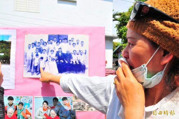 57歲教友陳秋華指著這張拍攝於半世紀前的老照片,年輕的潘世光神父替大她12歲的姊姊當主婚人,自己當時才6、7歲,哭著說感謝神父對全家的照顧。(記者花孟璟攝)