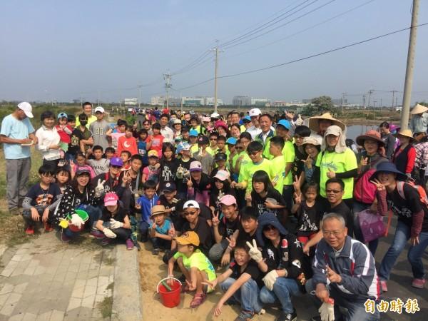 台江NGO老中青三代師生響應世界森林日,參與淨堤植樹。(記者蔡文居攝)