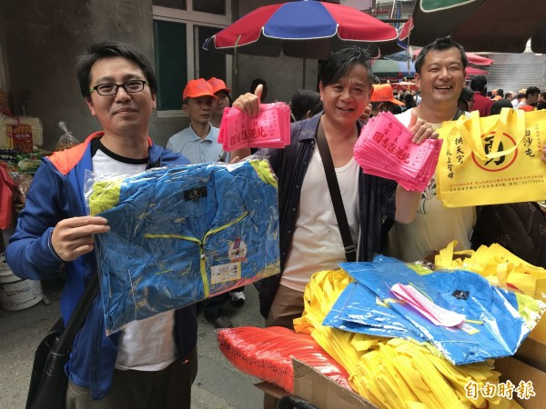 三位遠從台北市來報名的信眾,一口氣完成一百多位親友報名,高興地秀出制服及臂章等物。(記者張勳騰攝)