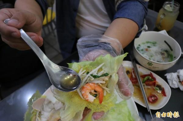 吃越南蛋餅要以生菜包裹餅皮,再陸續放入配料及醬汁。(記者鄭名翔攝)