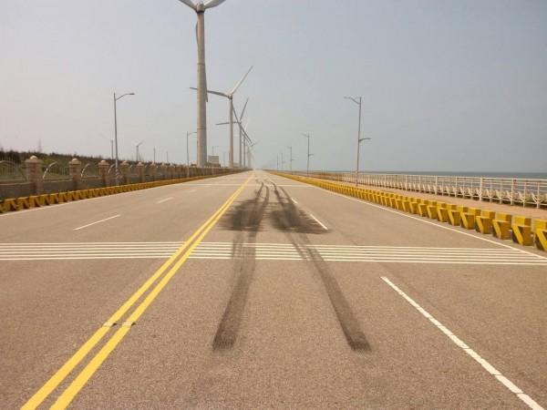 陳嫌上月31日駕駛野馬跑車在台中港環港北路與重機競速,燒胎,地面留下長長黑色胎紋。(記者歐素美翻攝)