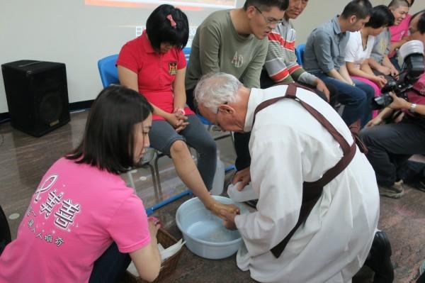 吳道遠神父行濯足禮,為美善基金會服務對象洗腳。(記者蔡文居攝)