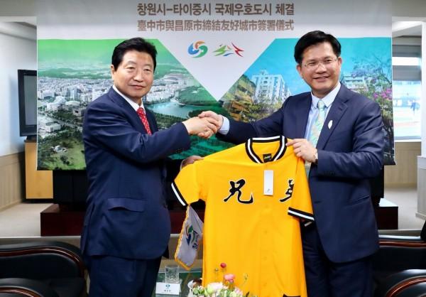 台中市長林佳龍(右)致贈昌原市長安商守一套中信兄弟隊球衣。(台中市政府提供)