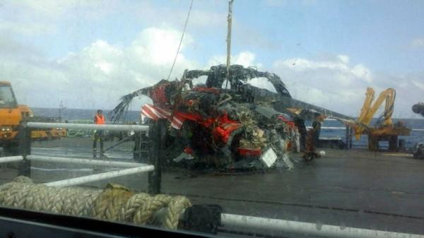 墜海黑鷹直升機被打撈上工作平台,殘骸內發現的2具遺體身分待査。(民衆提供)