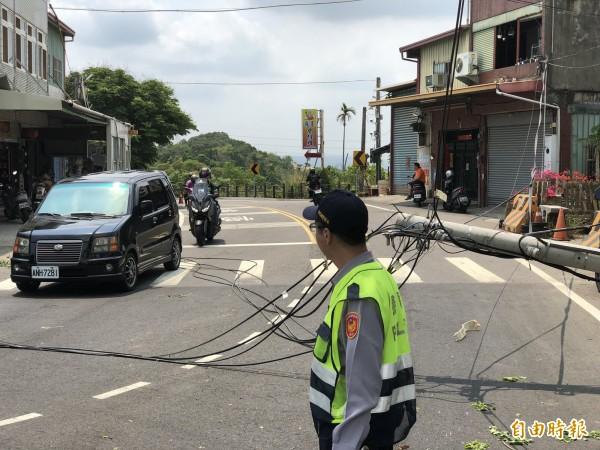 這支電線桿才因被扯斷換新,不料不到半年,今天又被資源回收車扯斷,警方派員疏導交通。(記者湯世名攝)