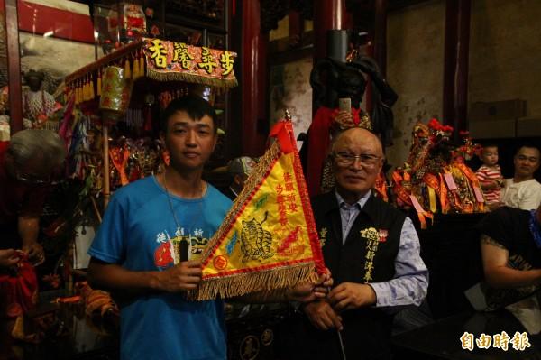 張東耀(左)背著媽祖神像徒步行腳到奉天宮,由董事長何達煌(右)接待。(記者林宜樟攝)