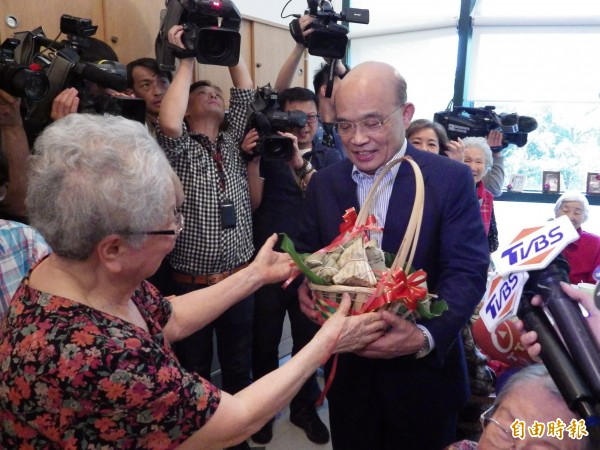 前行政院長蘇貞昌今天下午到新北市三芝雙連安養中心進行「訪老朋友談新希望之旅」,長者熱情送上象徵包中的粽子。(記者陳心瑜攝)