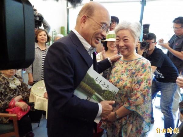 在雙連安養中心擔任志工的74歲油畫家陳豐美(右)送給71歲的蘇貞昌自己的畫作集《七十之美》。(記者陳心瑜攝)