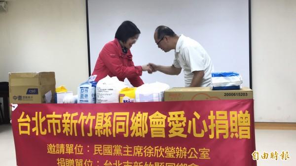 民國黨主席徐欣瑩(左)把她在3月11日晚,跟柯P一起在竹北夜市義賣古早味粉圓的所得也一併捐出,由「由根山居」主任周神助(右)代表接受。(記者黃美珠攝)