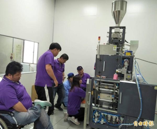 日本技師現場教導庇護工廠員工使用新包裝機。(記者陳冠備攝)
