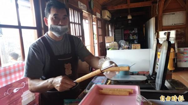 用特製鐵條將烤好的蛋餅皮捲成長條狀,就大功告成了。(記者廖淑玲攝)