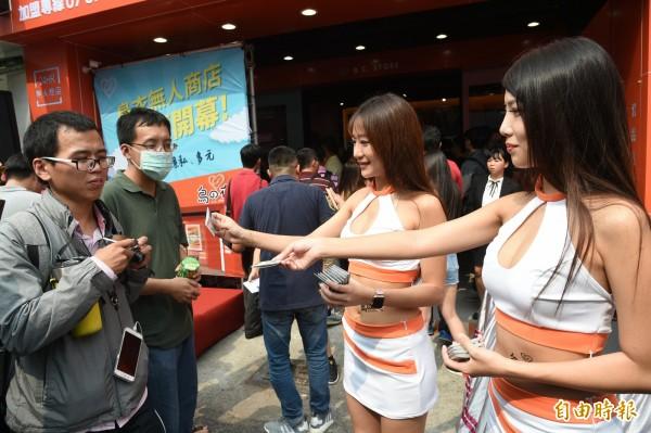 無人商店業者今天派出辣妹走上街頭宣傳發保險套,有些男生害羞不敢伸手拿。(記者張忠義攝)