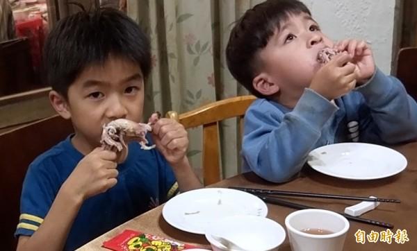 溪頭妖怪村「蝴蝶雞」一上桌,小朋友雙手及嘴巴忙著一口接一口品嚐。(記者謝介裕攝)