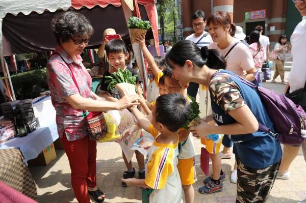 小朋友拿著自己種的蔬菜,向民眾推銷。(記者蔡淑媛翻攝)