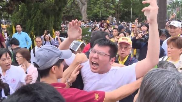 前駐韓外交官劉順達(黃帽者)從後方拉扯潘姓學生衣領,造成潘生被勒頸。(記者陳薏云翻攝自YouTube)