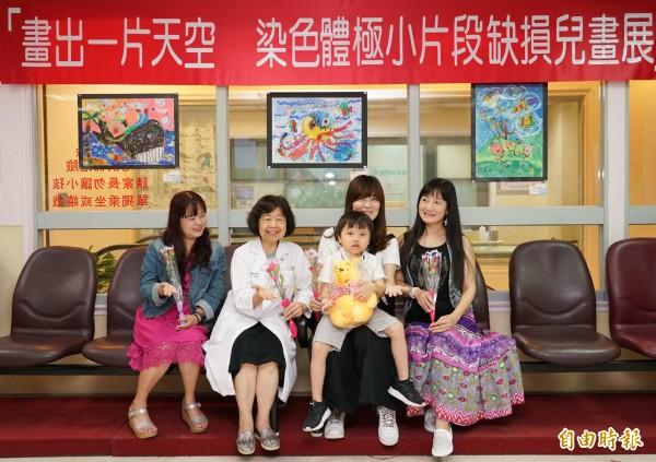 將滿7歲的陳柏丞由母親梁嘉妮抱著出席彰基兒童醫院畫展,讓大家分享他一幅幅的美麗畫作。。(記者湯世名攝)