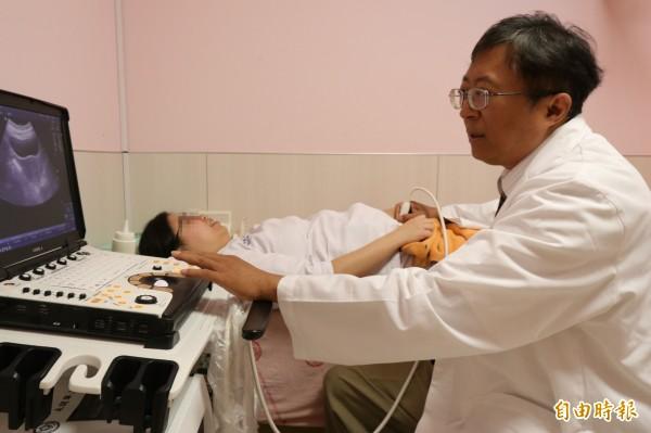 亞大醫院婦科主任陳泰昌以超音波替患者檢查子宮肌瘤,提醒少吃油炸燒烤類、生冷等食物,多吃蔬菜水果,就能降低罹患子宮肌瘤機率。圖中患者非當事人。(記者陳建志攝)