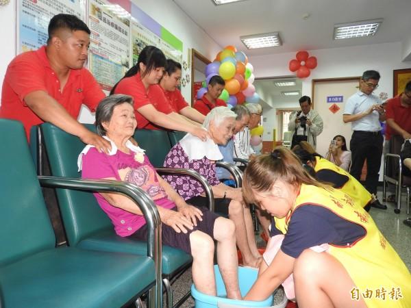 草屯療養院老年日間病房舉辦母親節活動,讓銀髮長輩體驗洗腳、肩頸按摩的雙重享受。(記者佟振國攝)
