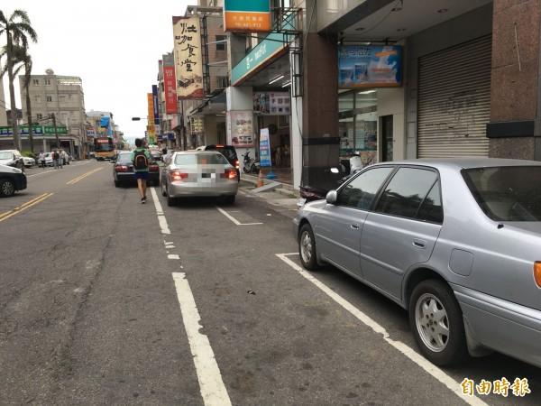 竹南鎮市區停車位一位難求,常有車主違規並排停車,導致人車爭道交通問題。(記者鄭名翔攝)