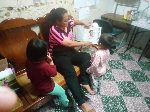 小芬媽媽在家務服務時,與小朋友分享繪本故事。(圖由台灣世界展望會提供)