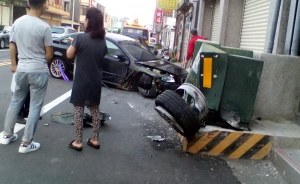 小客車自撞變電箱,車頭受創嚴重,右前輪卡在變電箱上。(記者張勳騰翻攝)
