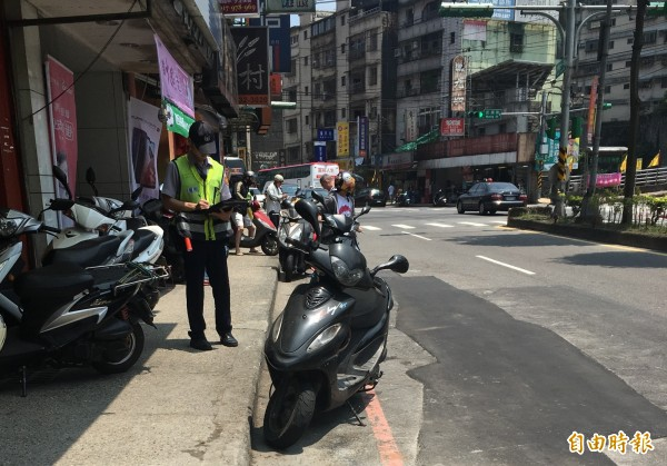 排隊辦理門號的民眾將機車違停在紅線與人行道之間,警方依法開罰。(記者吳昇儒攝)