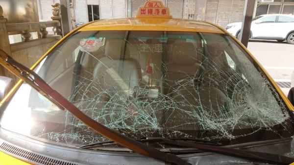 計程車遭到池魚之殃,擋風玻璃及引擎蓋全毀。(記者吳昇儒翻攝)