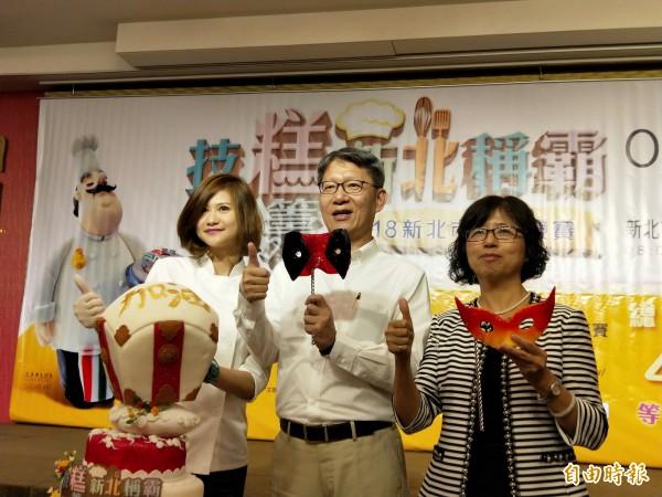 新北市副市長葉惠青(中)在裴志偉(左)以平溪天燈為造型設計的的翻糖蛋糕上,以金糖寫下「加油」兩字,右為勞工局長許秀能。(記者何玉華攝)