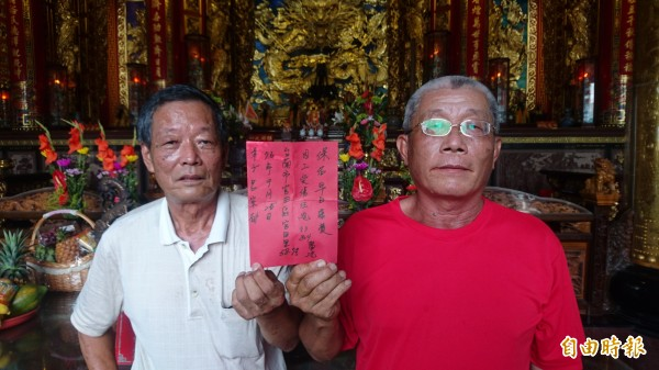 呂宗郁的父親呂丁發(右)展示到官田慈聖宮祈求兒子康復的許願紅紙,由廟祝陳天進(左)將許願紙供奉在神農大帝前。(記者楊金城攝)