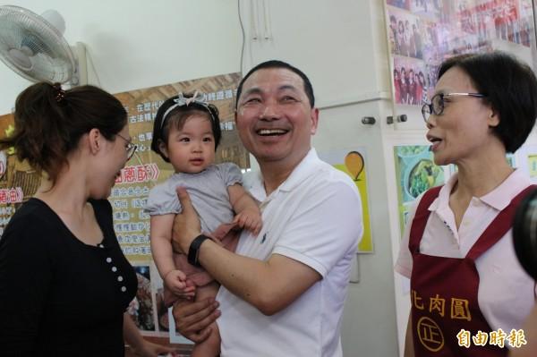 新北市副市長侯友宜抱起正彰化肉圓業者的孫子,小朋友不怕生,笑得很甜,給足侯友宜面子。(記者張聰秋攝)