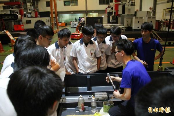 內思高工機械科建教班參與亞崴機電產學合作計畫的學生(圖右著藍色上衣者)把從師傅那裡學來的技術,跟學弟妹們分享,儼然成了實習課的小老師。(記者黃美珠攝)
