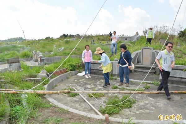 彰化市八卦山第二公墓稜線遭違法架設長度達300公尺的超大型鳥網,稽查人員以鐮刀拆除。(記者湯世名攝)
