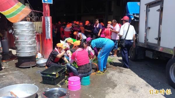 信徒伙食團忙著洗菜、切菜。(記者廖淑玲攝)
