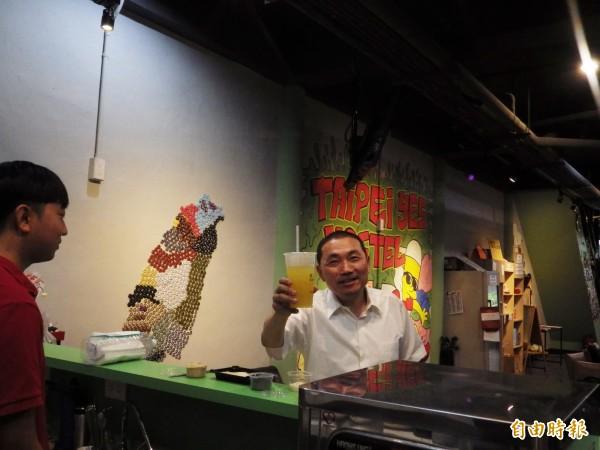 侯友宜今天到參訪淡水第一家青年旅館「Taipei Yes Hostel」,和八年級老闆郭立恆(左)談青年創業,品嘗淡水美食。(記者陳心瑜攝)