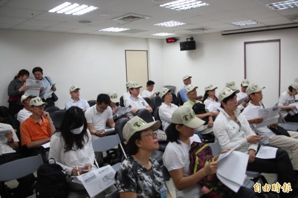 市府今天召開大灣北段說明會,現場來了約30位居民,頭上都戴著「官逼民反」的帽子,抗議市府收回饋金毫無道理。(記者鍾泓良攝)