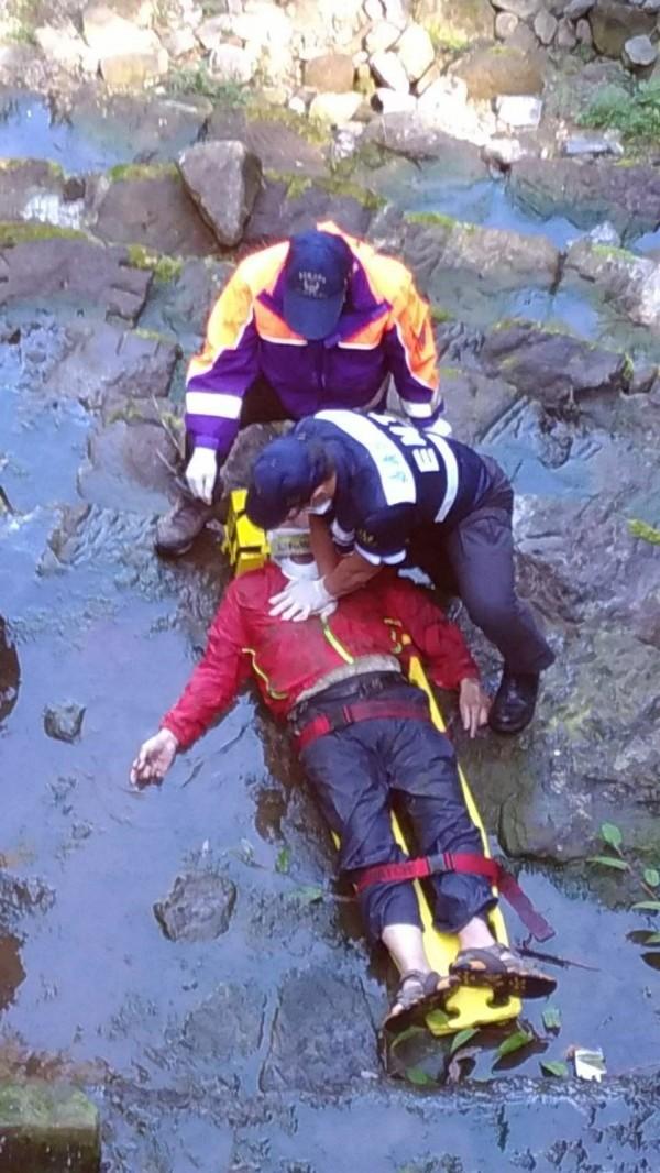 救護人員為墜傷男子急救,正送醫搶救中。(記者王善嬿翻攝)
