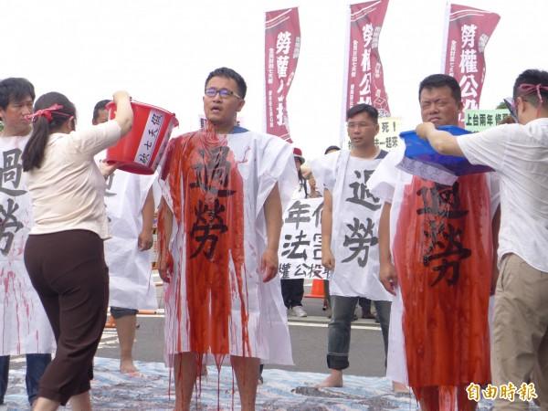 勞權公投聯盟上演行動劇,血色液體澆身,象徵勞工的血汗。(記者李雅雯攝)