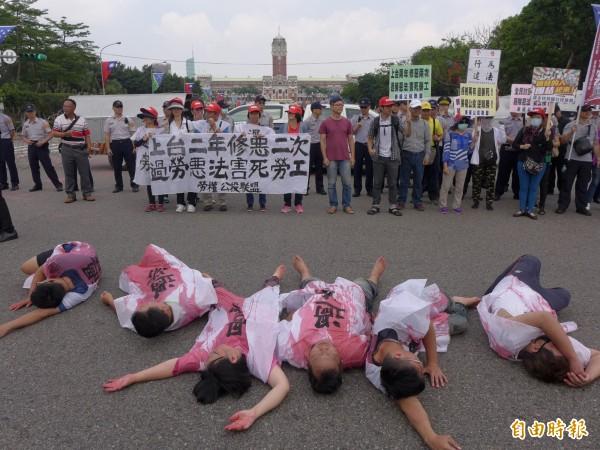 勞權公投聯盟上演行動劇,在總統府前倒下,代表台灣勞工面對的過勞死風險。(記者李雅雯攝)