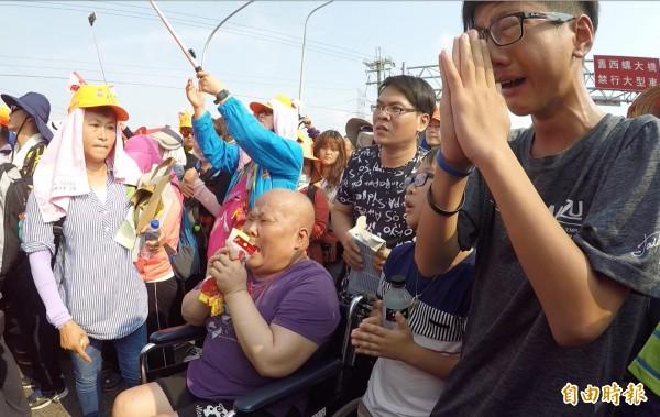 正在接受癌症治療的廖婦無懼病痛,坐著輪椅祈求鑽轎腳,一旁孫子也哭求媽祖保佑,情景令人動容。(記者陳冠備攝)