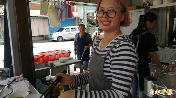 鄭華書正在煮麵,老公黃良淦(左)忙進忙出。(記者花孟璟攝)