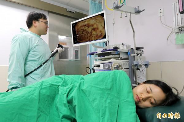 亞大醫院肝膽胃腸科主治醫師江承源,以大腸鏡檢查接受「糞便移植」後,患者腸道狀況。示意圖非文中本人。(記者陳建志攝)