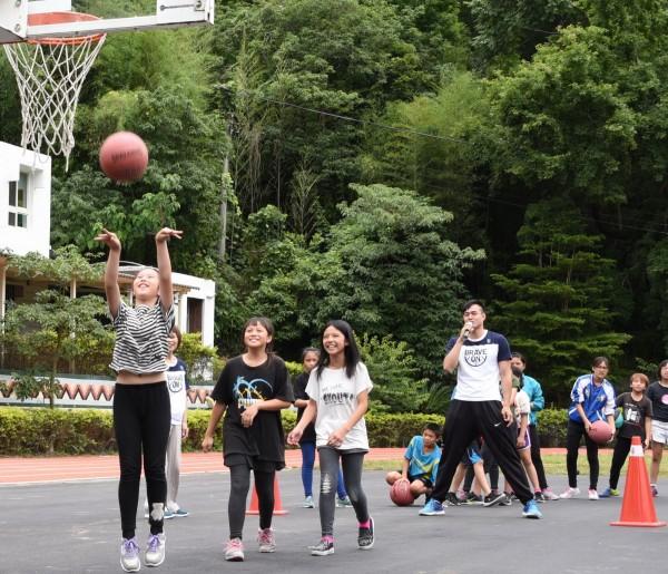 富邦勇士球員為梅園國小學童舉辦籃球派對,指導學童打籃球。(富邦慈善基金會提供)