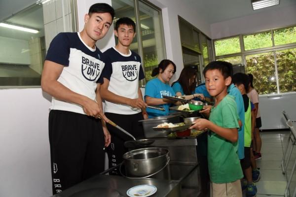 富邦勇士隊張伯維(左一)、張書維(左二)為小朋友營養午餐打菜。(富邦慈善基金會提供)