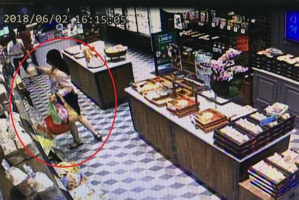 監視器拍下阮女偷偷將架上吐司收入自己的手提袋內。(記者徐聖倫翻攝)