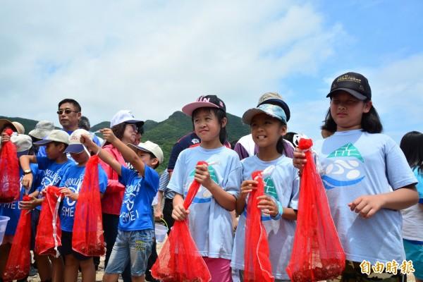新北市政府在貢寮卯澳灣舉辦舉辦放流活動,圖為學生拿著九孔苗準備放流。(記者俞肇福攝)