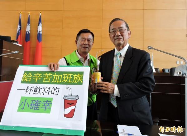 市議員鄭功進(左)送副市長林陵三1杯飲料,呼籲市府縮短停車收費時間,給加班族小確幸。(記者張菁雅攝)