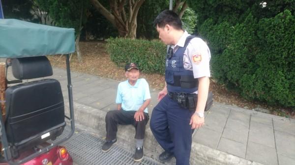 魏姓老翁在國軍桃園總醫院區騎乘電動代步車迷路,且疑有中暑情形,員警見狀立刻將他攙扶到路旁休息。(記者許倬勛翻攝)