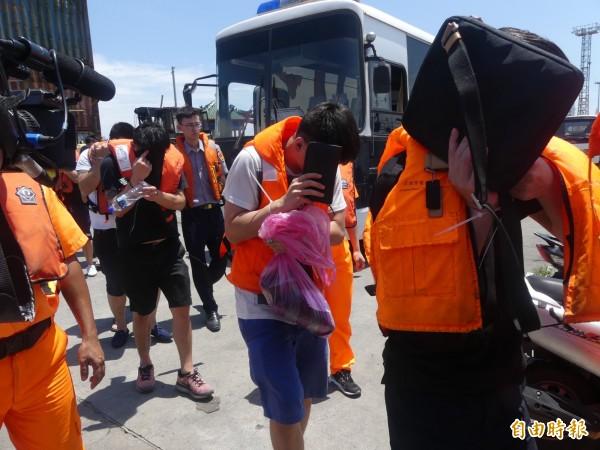 幹員在金門海巡人員協助下,昨天將詐騙集團成員隨車押至料羅碼頭。(記者吳正庭攝)