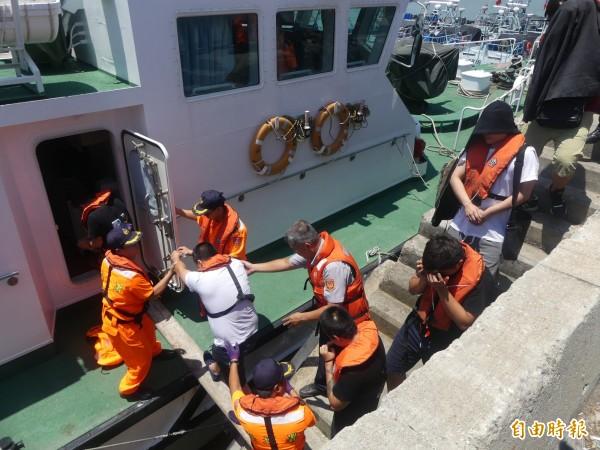 刑事局幹員昨天將詐騙集團成員押至料羅碼頭登船。(記者吳正庭攝)