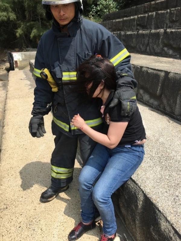 王女獲救時情緒仍十分低落,抱著消防員痛哭。(記者鄭名翔翻攝)
